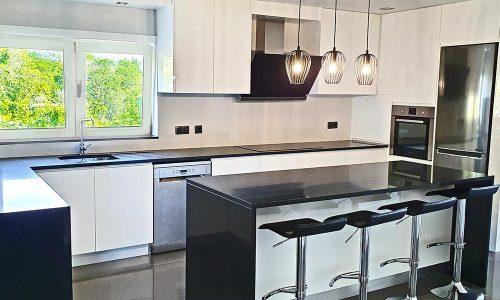 Küche mit poliertem schwarzen Granit und Neolith Arctic White als Wand